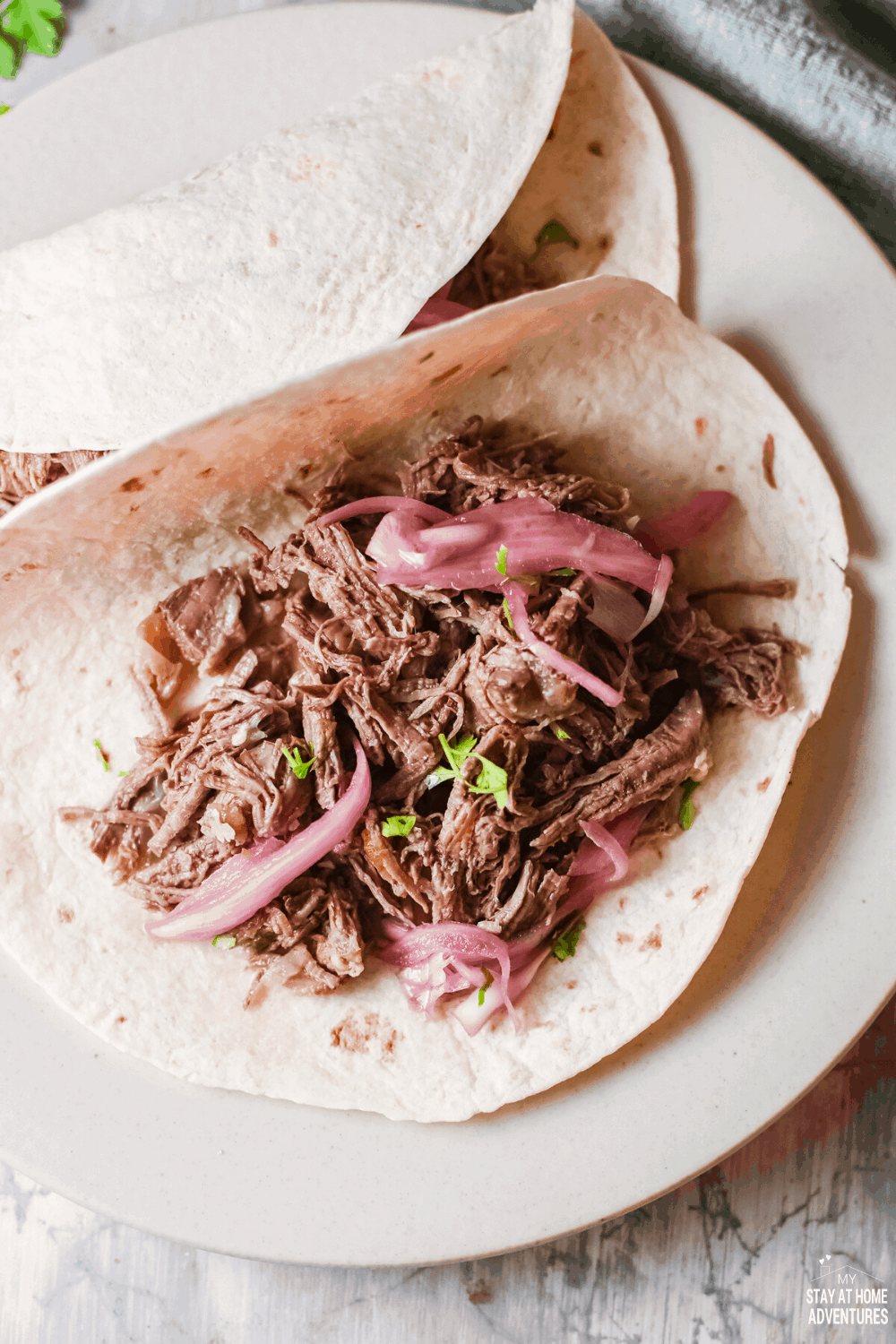 Shredded beef tacos (tacos de Carne Deshebrada) are tender, flavorful, amazing tacos that your family will ask for time and again. #tacos #tacosdeshebrada #shreddedbeeftacos #tacotuesday via @mystayathome